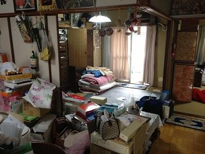 家の間取りは、和室が2部屋、洋室1部屋に台所の3DK。鍵をお預かりし、スタッフ3名9:00より作業開始。押入れには、たくさんの布団、扇風機・アイロンなどの家電品、贈答品、洋服(衣装ケース6箱)、 趣味の道具がぎっしりと つめ込められていました。 布団・衣類・家電品・ガラス製品陶器・道具類・贈答品・プラスチック類に仕分けをして運び出し作業。 もう一部屋の和室には、 すべての引き出しが洋服でいっぱいの大きな洋服タンスが2台。 趣味の作品や調度品飾ってある飾り棚が1台ありました。こちらも、衣類・飾り棚のガラス扉・タンスに付属している鏡(取外し)・ 木製のテーブル・紙類(本・新聞紙)に仕分けをして運び出し作業。台所にかけては、冷蔵庫、電子レンジ 食器棚、ダイニングテーブル、食品類が中心にありました。家電品・陶器・ガラス・木製品に仕分けを行います。缶詰や飲料類は、すべて中身をだして缶・瓶・ペットボトルに仕分けます。 洋室には、健康器具、空気清浄器といった家電品のほか、洋服タンス(中)が1台、3段ボックスなどありました。 こちらの仕分け作業中には、アルバム、パスポート、現金などの貴重品がタンスの引き出しから見つけ出すことができました。 当社では、作業中に見つかった貴重品や探し物が見つかったものは、思い出BOXへ厳重に保管しています。 また、作業中に必要なのか不要なのか判断に迷ったものは、随時電話にてご連絡をしています。 ベランダには、趣味の道具や作品が詰められた段ボールが20箱のほか、未使用ままの掃除機、壊れたストーブなどが積み重ねられている状態でした。 2年間、雨風に打たれた段ボールの一部はボロボロに劣化していました。 すべてものを運び出した後、しっかり清掃作業を行いました。 16:00作業完了。 作業時間6時間 スタッフ3名